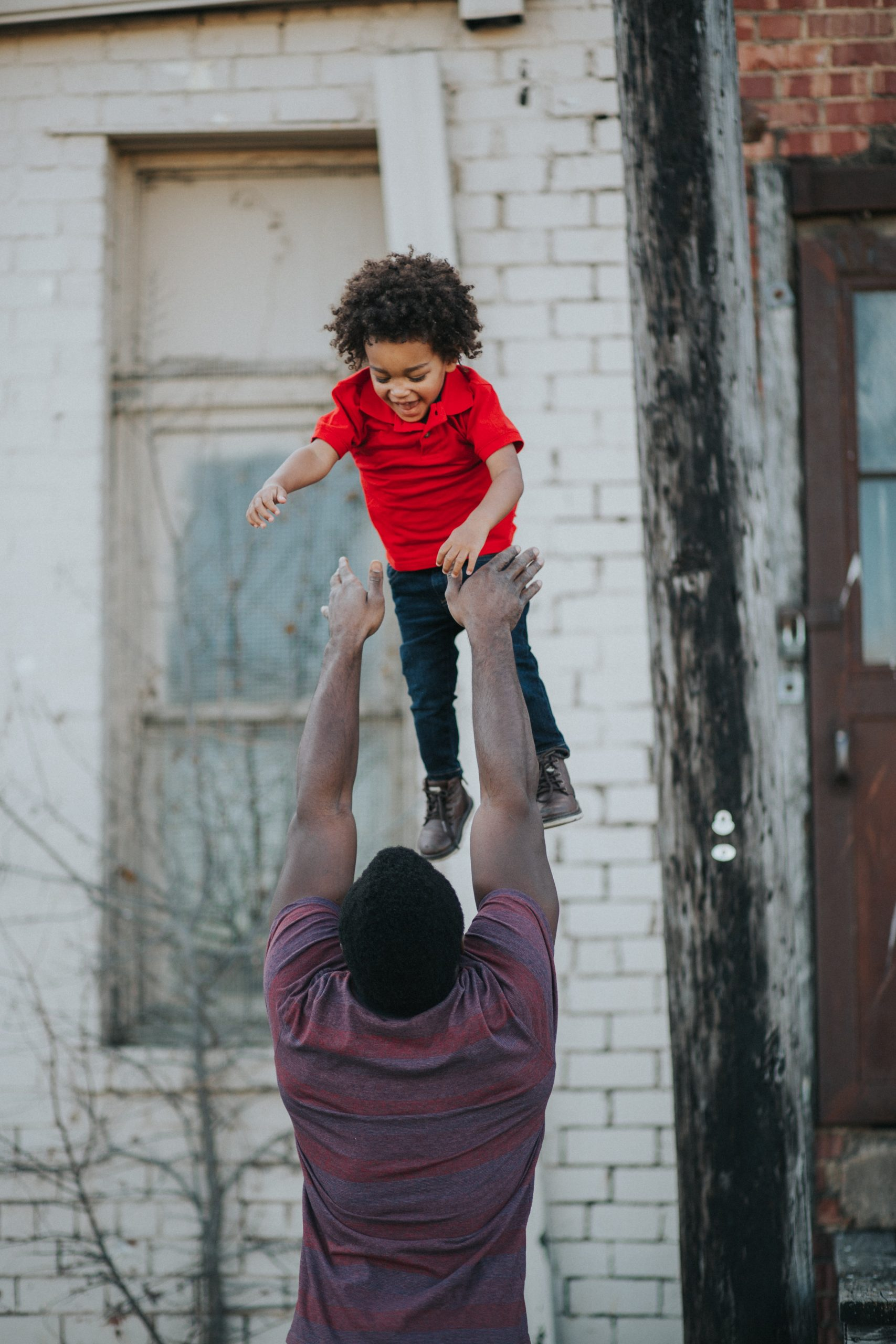 Deeply hued Black man in maroon shirt playfully throwing son in the air.